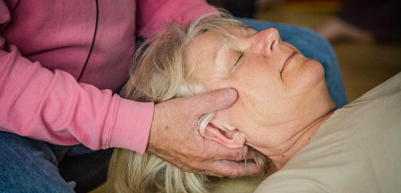 Dame bei einer Feldenkrais Einzelbehandlung. Ihr Kopf liegt in zwei Händen, sie hat die Augen geschlossen.