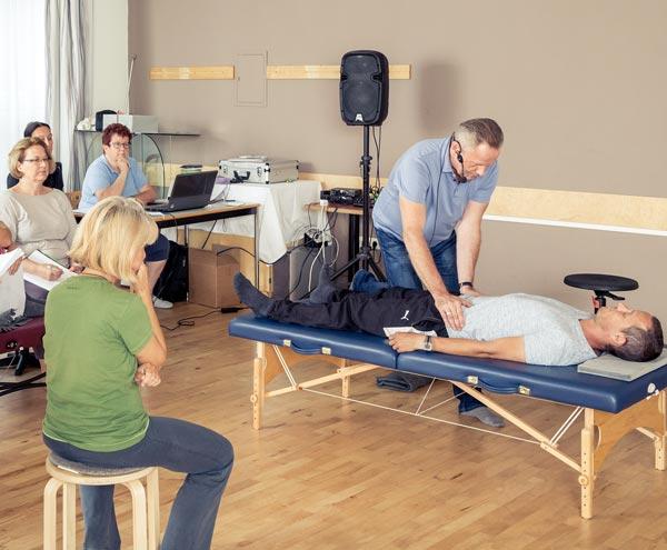 Personen bei Feldenkrais-Ausbildung in Seminarraum. Kajetan Schamesberger behandelt eine Person.