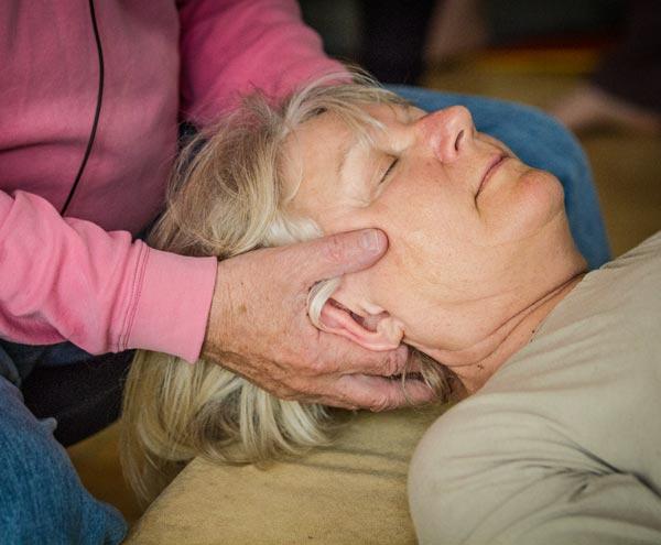 Foto von Dame bei einer Feldenkrais Einzelbehandlung. Ihr Kopf liegt in zwei Händen, sie hat die Augen geschlossen.