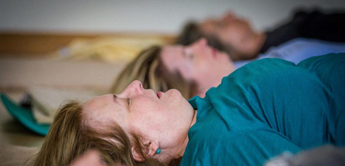 Personen liegen am Rücken auf Matte bei Feldenkrais-Kurs in Seminarraum
